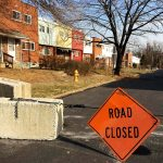 orange road closed sign hanging in middle of street. Can see colorful, newer row homes.