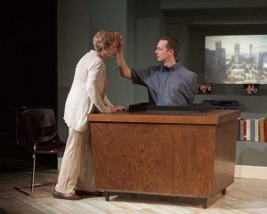 Man with blue collared shirt appears popping out of a wooden desk. The clean-cut man has one arm that touches the forehead of Anne, an older woman dressed in beige.