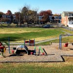 green grass in bckground, playground in foreground. Blue sky, rowhomes behind it.
