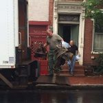 two white men loading a truck with what appear to be old chairs. They stand outside a red brick home